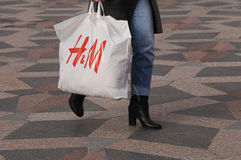 CONSUERS MIT SCHWEDISCHER EINKAUFSTASCHE DER KETTEN-H&M Lizenzfreie Stockfotografie