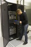 IT Consulant Install Blade Server. A working IT engineer / technician installing a blade server in a rack at the data center stock photos