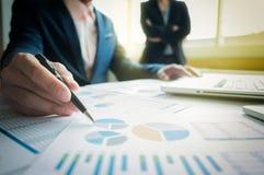 Consulente aziendale che analizza le figure finanziarie che denotano il progre immagine stock