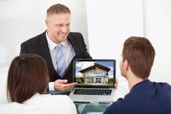 Consulente che mostra l'immagine della casa alle coppie sul computer portatile fotografie stock