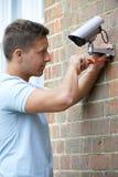 Consulente di sicurezza Fitting Security Camera per alloggiare parete Fotografia Stock