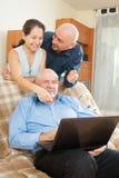 Consulente e coppie sorridenti con il computer portatile Immagine Stock