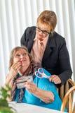 Consulente finanziario Handing Scissors a signora senior Holding Credit Cards fotografia stock