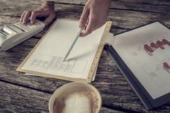 Consulente finanziario maschio che indica con la penna i dati statistici numerici Fotografia Stock