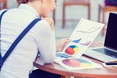 Consulente in materia di investimento che analizza rapporto finanziario annuale della società Fotografia Stock
