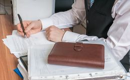 Consultant or adviser writing in office Stock Photos