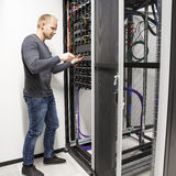 IT consultant building network rack in datacenter. IT engineer or technician working with network cabling and installation communication switches in datacenter royalty free stock photos