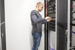 Consultant builds communication rack in datacenter Royalty Free Stock Images