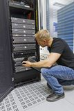 IT Consultant Checks SAN. It engineer / consultant working in a data center. Holding a disk cabinet front and look at the disks. This enclosure in a SAN (storage Royalty Free Stock Photography