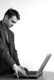 Consultant concentrated on laptop. Standing,white young man in jacket is working on his laptop - black& white royalty free stock photo