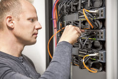 IT consultant connecting network cable into switch. IT engineer or technician working with network cabling and installation of communication switches in royalty free stock images
