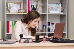 Consultant cosmetics earned a laptop in an office. A young girl puts makeup in the office workplace Stock Photo