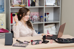 Consultant cosmetics happy working in the office. Young woman sitting at office table, laid out on the table cosmetics Royalty Free Stock Image