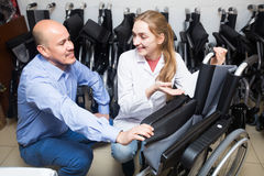 Consultant and customer in orthopaedic store. Young female consultant offering manual wheelchairs to customer in orthopaedic store stock photos