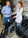 Consultant and customer in orthopaedic store. Young female consultant offering manual wheelchairs to customer in orthopaedic store. Focus on man Stock Photo