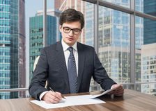 Consultant is dealing with due diligence process in a modern skyscraper office with a panoramic Moscow city view. Stock Photos