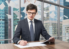 Consultant is dealing with due diligence process in a modern skyscraper office with a panoramic Moscow city view. P Royalty Free Stock Photography