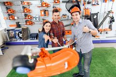 A consultant in a garden tools store shows a customer a grass cutter. royalty free stock image
