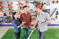 A consultant in a garden tools store shows a customer a grass cutter. stock photos