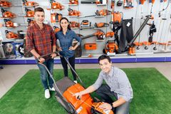 A consultant in a garden tools store shows a guy and a girl a lawn mower. Royalty Free Stock Images