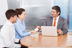Consultant Giving Card To Couple Stock Image