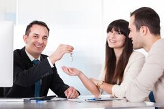 Consultant giving keys to couple Royalty Free Stock Photos