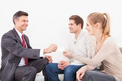 Consultant giving visiting card  to couple. Happy Male Consultant Giving Visiting Card To Young Couple Stock Photo