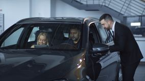 Consultant helping family with car choice. Dealer in auto salon helping cheerful couple with kids with car exploration before purchasing Royalty Free Stock Photos