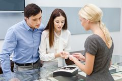Consultant helps couple to choose jewelry Royalty Free Stock Image