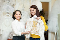 Consultant helps to girl chooses  bridal clothes Royalty Free Stock Photo