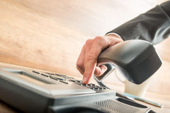 Consultant holding the receiver of a desk phone while dialing. Consultant holding the receiver of a corded desk phone while dialing, in the office Stock Photography