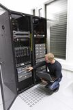 IT Consultant Maintains Backup in Datacenter. It engineer / consultant working in a data center. Maintain backup. Monitoring with laptop Stock Photography