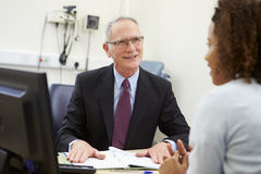 Consultant Meeting With Patient In Office Stock Photo