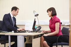 Consultant Meeting With Patient In Office Stock Images
