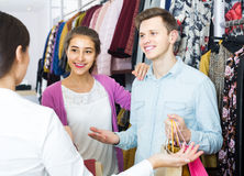 Consultant offering customers autumn clothes in shop Stock Photo