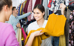 Consultant offering customers autumn clothes in shop Royalty Free Stock Images