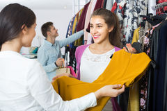 Consultant offering customers autumn clothes in shop Royalty Free Stock Photo