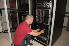 IT consultant performs work in a data center. The room is filled with servers and other related equipment Stock Photos