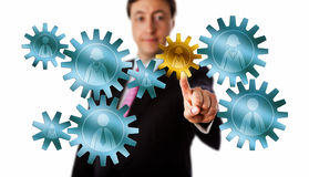 Consultant Picking A Worker Cog In A Gear Train. Smiling recruitment consultant is picking a female worker icon embossed on a golden cog in a mission critical Stock Photos