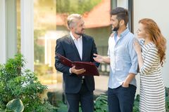Real estate consultant presenting offer. Consultant of real estate market presenting offer of apartments in neighborhood to young couple Stock Image