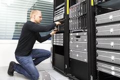 It consultant replaces harddrive in datacenter storage Royalty Free Stock Photo