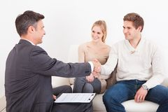 Consultant shaking hand with customer. Male Consultant Shaking Hand With Young Couple At Home Royalty Free Stock Images