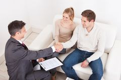 Consultant shaking hand with customer. Male Consultant Shaking Hand With Young Couple At Home Royalty Free Stock Photos