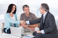Consultant shaking hand with woman. Portrait Of Mature Consultant Shaking Hand With Happy Woman Royalty Free Stock Image