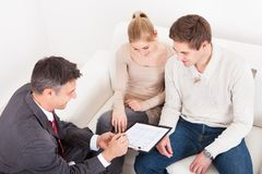 Consultant showing agreement to couple. Male Consultant Showing Agreement To Young Couple At Home Stock Photography