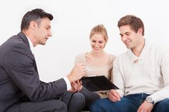Consultant showing clipboard to couple. Male Consultant Showing Clipboard To Happy Young Couple Royalty Free Stock Photo