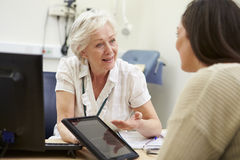 Consultant Showing Patient Test Results On Digital Tablet Stock Photos