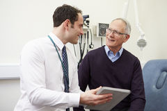 Consultant Showing Patient Test Results On Digital Tablet Stock Images