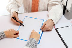 Consultant is showing. A consultant is showing some documents to client Royalty Free Stock Image