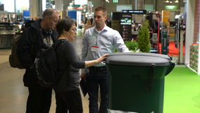 Consultant in the store demonstrates new high-tech container for sorting and disposing of garbage. HELSINKI, FINLAND - APRIL 07, 2017: Consultant in the store stock video